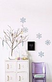 Festively decorated twigs in glass vase on white-painted cabinet against wall with bluish snowflake motifs and purple plexiglass chair with cushion