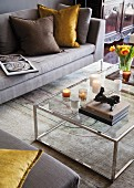 Small sculpture on stacked books and candles on glass and chrome coffee table; sofa, scatter cushions and rug in elegant shades of grey and brown