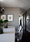 Artistic plant arrangements on dining table and Ghost chairs; framed artworks on taupe-painted wall and hallway to one side in background