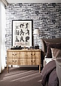 Wallpaper patterned with small black and white architectural pictures in elegant bedroom; framed poster of silhouettes on bedside chest of drawers