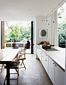 Open-plan kitchen with white, partition counter and access to terrace