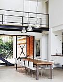 Offener Wohnraum mit Brücke im Obergeschoss, darunter Essplatz vor teilweise sichtbarer Treppe und Fensterfront zur Terrasse