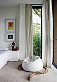 Snake made from wooden segments coiled around white beanbag in front of floor-to-ceiling window with white curtain in modern bedroom