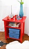 Books and blue cardboard boxes in bright red, open-fronted cabinet with various ornaments and accessories on top