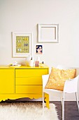 Yellow sideboard with curved base panel on flokati rug next to white plastic chair; white picture frames and picture of woman on wall