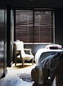 Postmodern armchair below window with closed louver blind in corner of bedroom