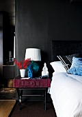 Bed & bedside table with table lamp against black wall