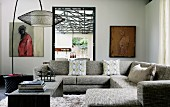 Comfortable, grey sofa combination and minimalist coffee table below jaunty arc lamp with mesh lampshade in corner of modern interior