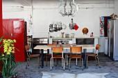 Tisch und Stühle im Retrostil vor Küchenzeile, an der Seite roter Schrank in loftartigem Wohnraum