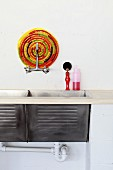 Simple sink with two basins and colourful trivet mat behind wall-mounted tap fitting