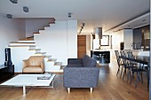 Open-plan living area in architect-designed house with minimalist furnishings and staircase without handrail