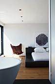 Blick von Bad Ensuite auf schwarzes Doppelbett mit weißer Bettwäsche und braunem Designer Butterfly Chair