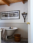 Wooden tub and free-standing bathtub against half-height, pale grey wooden panelling below framed picture on wall