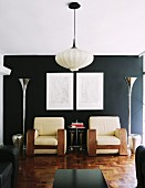 Pendant lamp with fabric lampshade in modern living room with chunky armchairs against black wall flanked by funnel-shaped designer standard lamps