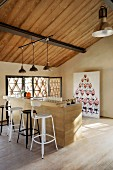 Various bar stools at wooden counter below group of pendant lamps suspended from wooden ceiling in attic interior