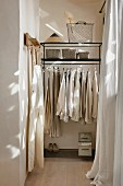 Men's clothing hanging from clothes rail in narrow niche with window