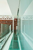 Loft gallery with glass floor and balustrade, steel joist structure against brick wall at far end and glass wall to one side