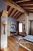Attic bedroom with rustic wood-beamed ceiling and walls painted white and lavender grey