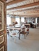 Blick durch offene Tür in grosszügigen Wohnraum mit verschiedenen Stühlen am Esstisch unter rustikaler Holzdecke