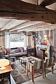 Chairs and comfortable couch below window in chalet interior with open fire
