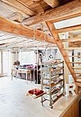 An Holzbalken aufgehängte Kinderschaukel neben rollbarem Regal mit Büchern in offenem Wohnraum einer Hütte