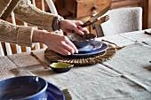 Frau deckt Tisch mit Gedeck & Bastuntersetzer