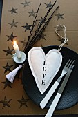 Decorative idea: Christmas tree candle holder clipped to twigs next to place setting with fabric heart and cutlery