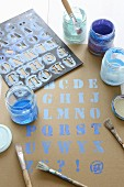 Letter stencil, paintbrushes and blue paint
