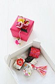 Small gift boxes decorated with tassels and pompoms