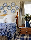 Schlafraum in Blau-Weiss mit Sammlung von Porzellantellern an der Wand über dem Bett