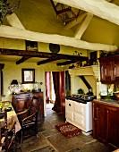 Landhausküche mit gelben Wänden, Holzschränken & Steinboden