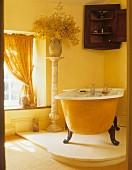 Gelbe freistehende Badewanne auf Podest in Bad mit gelben Wänden & Vorhängen