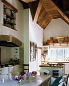 Landhausküche mit gewölbter Holzdecke, Esstisch mit Stühlen & Herd in gefliester Nische