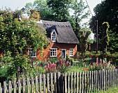 Blick auf Landhaus mit Reetdach und eingezäuntem Bauerngarten