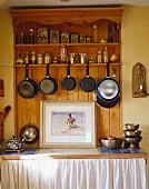 Aufgehängte Töpfe und Pfannen sowie Küchenutensilien in Küchenschrank aus Kiefernholz