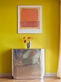 Blumenvase auf Metall-Kommode vor gelber Wand mit abstraktem Wandbild