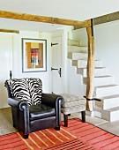 Wohnzimmer mit weißen Wänden, Steinfussboden, schwarzem Ledersessel & Steintreppe