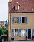 Fassade eines beigen Wohnhauses mit blauen Fensterläden (Frankreich)
