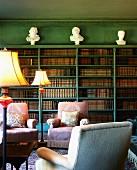 Grün getönte traditionelle Bibliothek mit Polstersesseln vor Bücherregalen