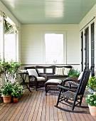 Dunkle Korbmöbel auf Veranda mit Blumentöpfen auf Holzdielenboden