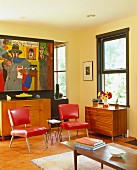 Living room with red chairs and colorful painting