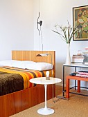 Bedroom with modern bed and Eero Saarinen side table