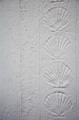 Muschelmuster in verputzter Wand