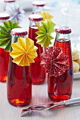 Small bottles of cherry drinks with paper rosettes