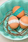 Drei Ostereier mit farbigen Borten auf rostigem, gebogenem Draht in hellblauer Schüssel