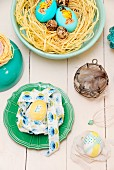 Various Easter nests of eggs, raffia and ribbons in bowls and on pale wooden surface