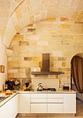 Modern, L-shaped kitchen counter, stone walls and vaulted ceiling