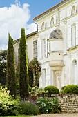 Fassade eines historischen, französischen Landgutes mit Zypressen und Buchskugeln hinter Natursteinmauer