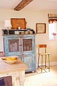 Vitrinenschrank im Vintagelook mit blauer Patina und Retro Kinderhochstuhl in einfacher Landhausküche