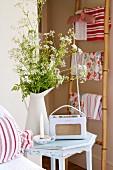Kofferradio im Retrostil und Wiesenblumenstrauss auf Nachttisch; Handtücher an Bambusleiter im Hintergrund